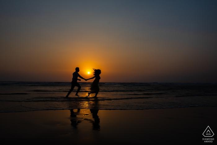 Photographe du Maharashtra avec un couple gambadant sur une plage de Goa alors que le soleil se couche derrière eux lors de cette séance photo avant le mariage