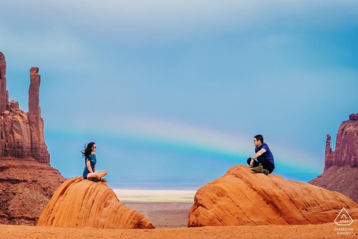 Verlovingsfotografie in Colorado   Het echtpaar bevindt zich in de Monument Valley, de regenboog verschijnt erachter.