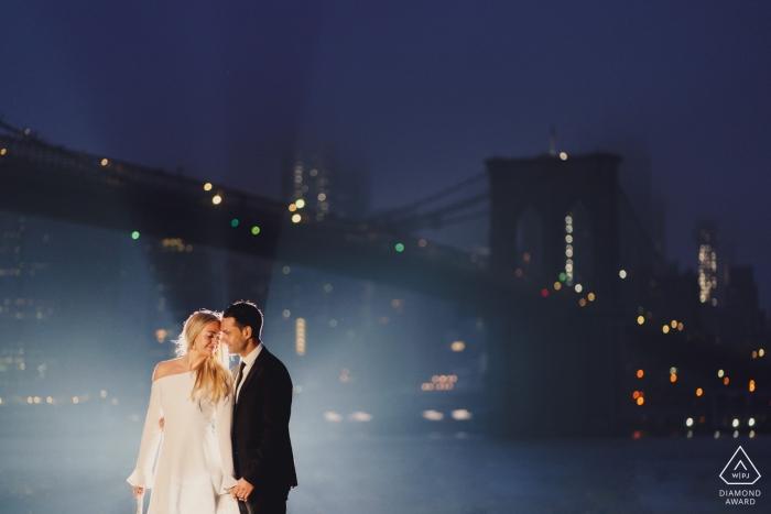 New York Couple back lit under the hudson brigde for engagement portrait