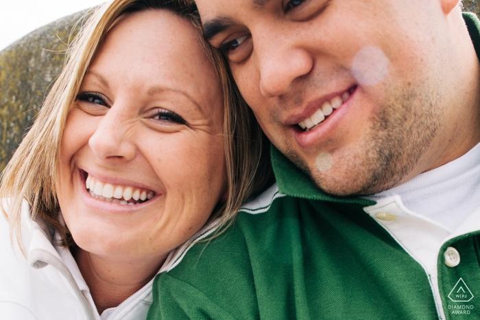 Photographie de mariage à Seattle dans l'État de Washington - Un couple nouvellement fiancé sourit et rit lors d'une séance de portrait