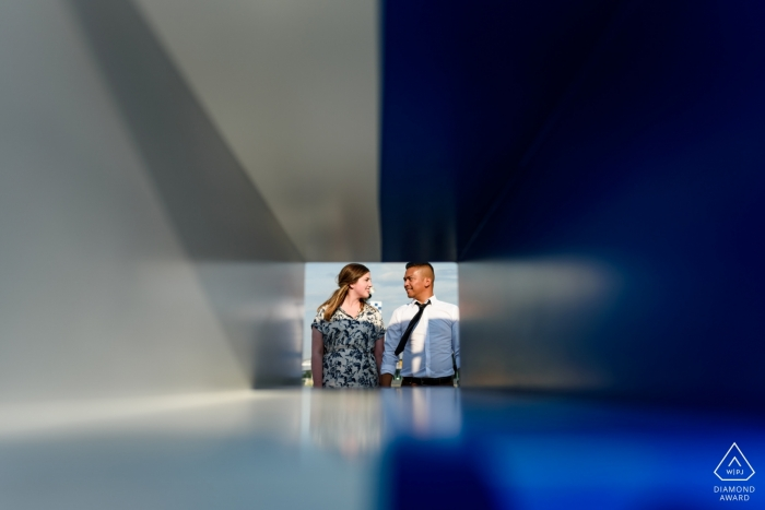 Photos de portraits du Vieux-Montréal - Photo de fiançailles géométrique d'un couple à travers une sculpture colorée