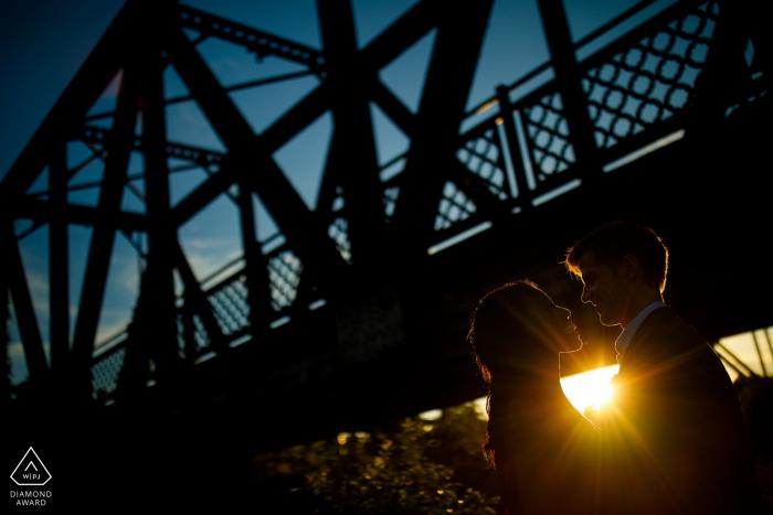 Il sole tramonta dietro una coppia e il Wynkoop Street Bridge a Denver. Fotografia di matrimonio CO