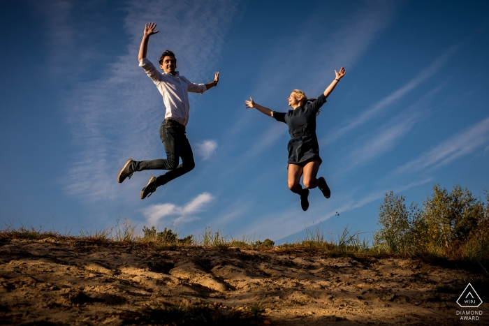 Stay Okay Bergen op Zoom engaged couple is jumping from a hill for a portrait