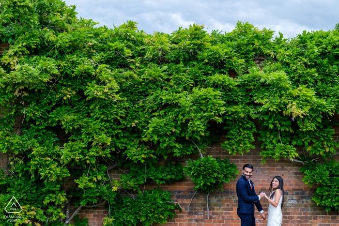 Nord-Mymms-Park-Paarsitzung gegen grüne Wand von Bäumen.