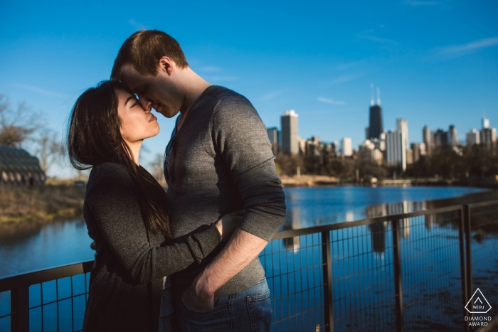 Couple hugs each other in a ray of sunlight in Chicago's Lincoln Park.