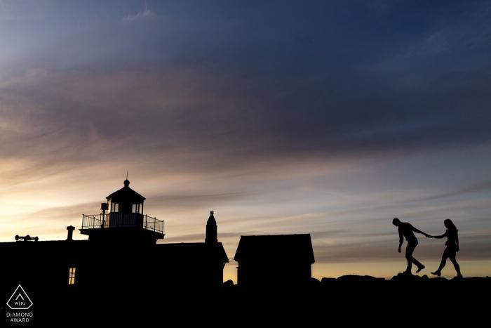 Discovery Park Engagement Photography - Un couple se promène sur des rochers près du phare