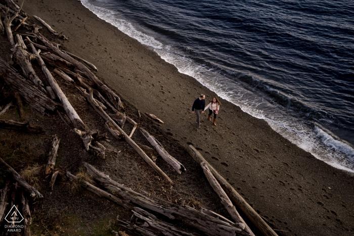 chambers bay engagement photo shoot - couple walk on the beach at chambers bay