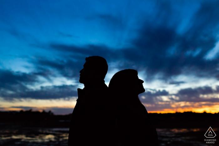 Odiorne State Park dans le New Hampshire Portrait avant le mariage - Le couple se découpe sur un ciel illuminé à la fin de leur séance de fiançailles à Portsmouth, New Hampshire