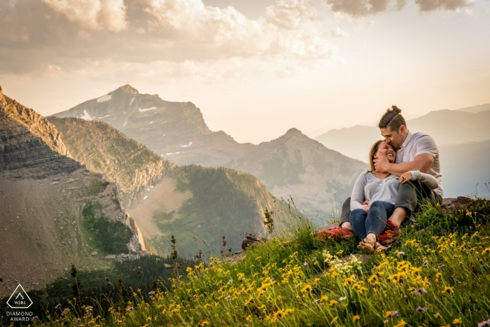 A couple sitting amongst the wildflowers at the Glacier National Park- Logans Pass