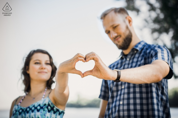 Un couple crée un cœur avec leurs mains lors de la séance photo d'engagement de Popowo Beach