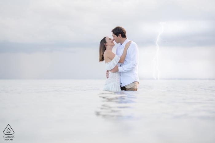 Het paar en de bliksem van Miami, Florida tijdens verlovingsspruit in het water.