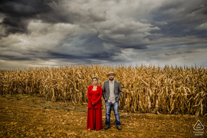 Couple stands for an engagement portrait in the foreground of a cornfield in Goiania, Brasil.