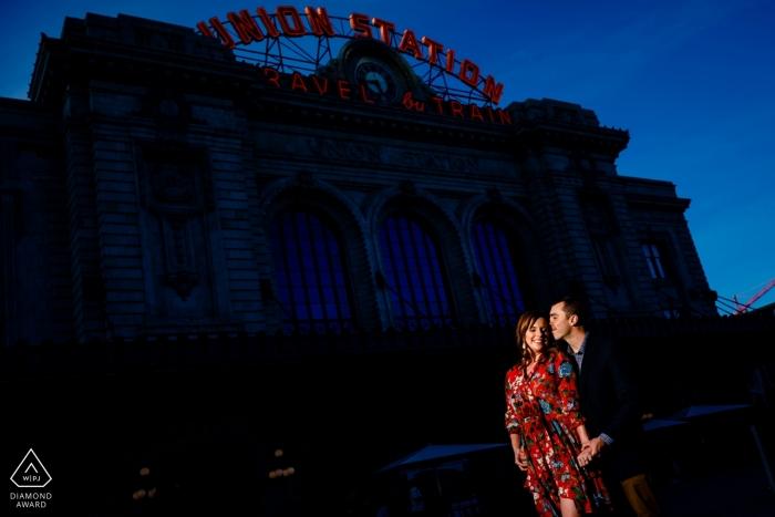 Usando un po 'di luce disponibile per evidenziare la coppia di fidanzati contro la Union Station nel centro di Denver durante una sessione di ritratti.