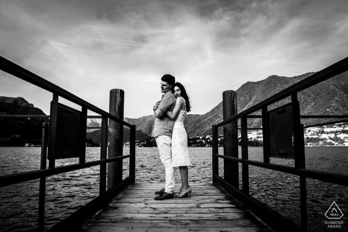 couple de lac como étreignant sur le quai au bord de l'eau pendant la séance photo de pré-mariage.