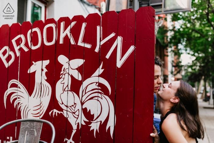 Sesja fotografii zaręczynowej na Brooklynie w Nowym Jorku z parą i pomalowanym czerwonym płotem.