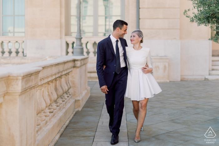 Un couple marchant dans les rues de Marseille lors de leur séance de photographie de pré-mariage pour des photos de fiançailles