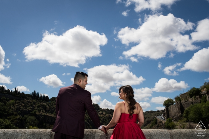 Engaged couple with cloudy sky background during prewedding photoshoot in Toledo, Castilla-La Mancha