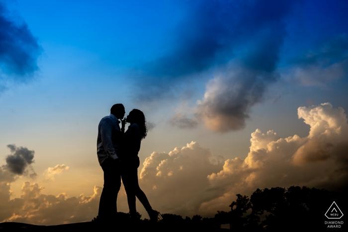 Photographe de portrait de fiançailles commémoratif Lincoln DC Washington DC créé la silhouette du couple debout sur le rebord