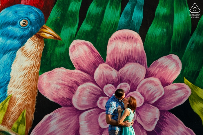 Couple kiss in front of a graffiti wall on Arthur Verona street in Bucharest during prewedding portrait session.