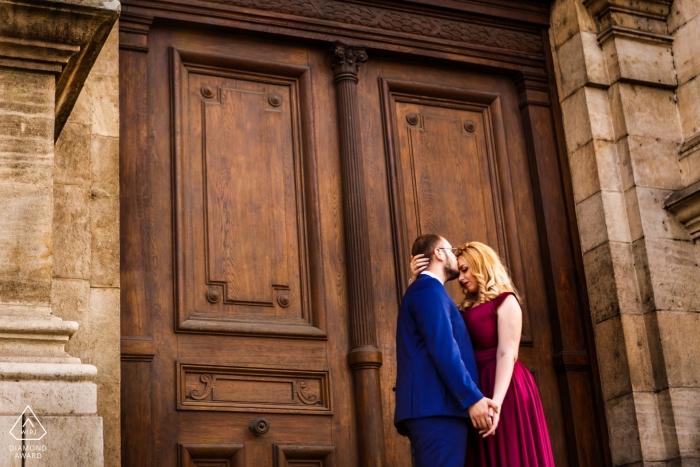 Zaręczona para całuje się przed głównym wejściem do zabytkowego budynku Sądu Apelacyjnego podczas sesji przedślubnej.