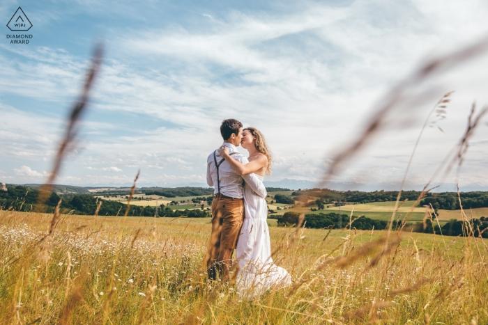 Marciac, Frankreich | Ein Paar, das in einer Landschaft während der Verlobungsfotosession im Gras küsst