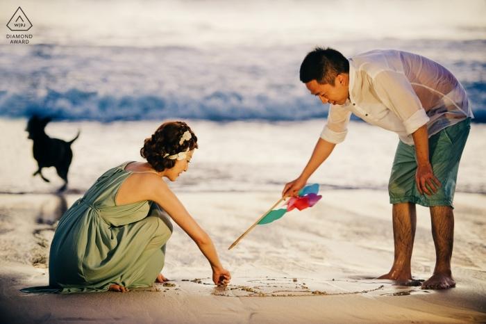 Photos de pré-mariage à Bali, Indonésie | Un couple joue le soir au bord de la mer, un chien court avec bonheur.