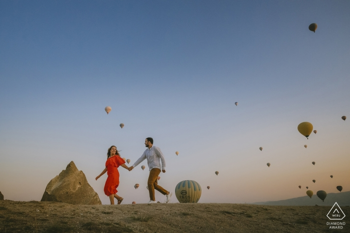 An engaged couple running in front of the balloons during portraits in Cappadocia Turkey
