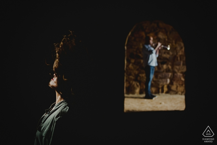 Engagement Photography for Zamora - Image contains: couple, arch, stone, hair, light, shadows, trumpet, horn