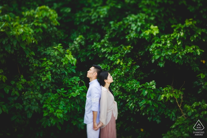 Engagement Photographer for Nanping - Image contains: couple, trees, green, portrait, holding hands, profiles