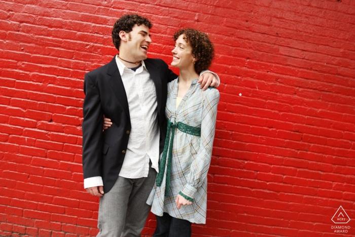 Verlobungsfotografie für Little Five Points, Atlanta   Paare, die zusammen vor roter Wand lachen
