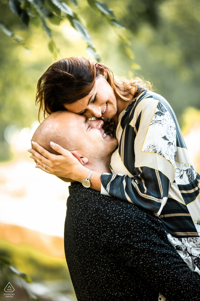 Engagement Portrait from Uniejow castle, Poland - The future groom lifts his beloved in his arms and hugs her cheek to her forehead.