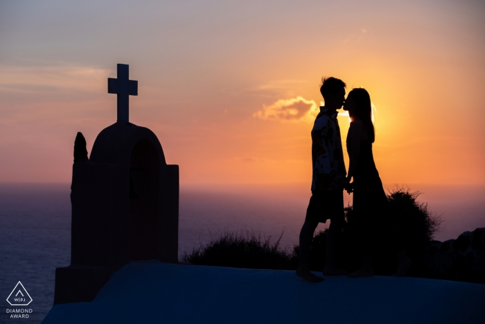 Engagement Photos from Santorini - Image contains: sunset, church, cross, silhouette