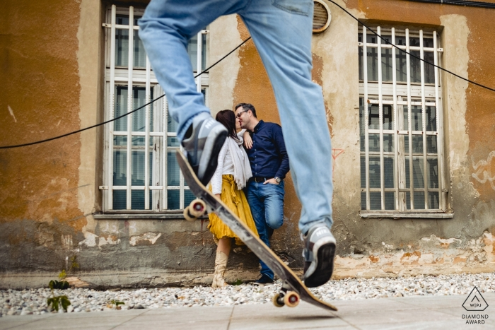 Engagement Photographer for Ljubljana Slovenia - a skater jumping in front of the kissing couple