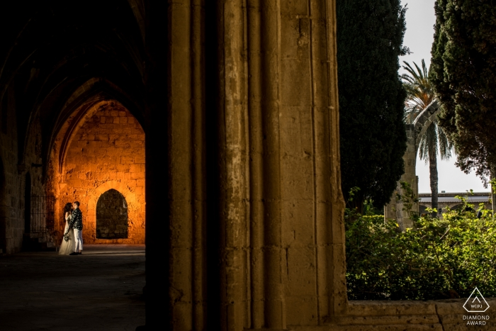 Engagement Portrait from Bellapais Monastery, Kyrenia, Cyprus - Couple is kissing in front of a highlighted wall