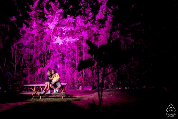 Güzelçamlı Kuşadası, Turkey Engagement Photography | Couple sitting on a picnic table looking each other and laughing and the background is highlighted with purple colour