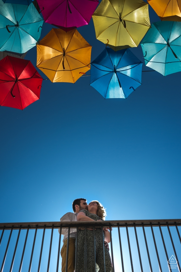 Bordeaux, France colorful umbrellas overhead in this engagement portrait of a couple