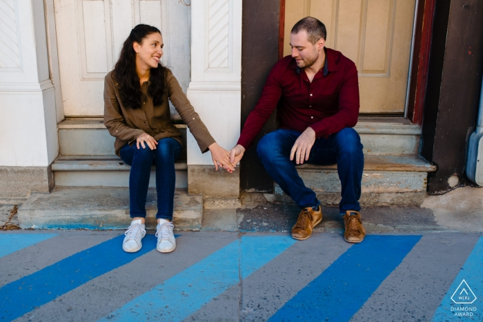 Montreal, Quebec Engagement photo of couple holding hands and sitting on front steps