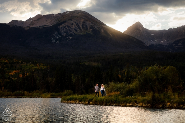 Verlobungsfotografie in Silverthorne, CO - Gehen Sie neben einem Teich entlang, während die Sonne über der Gore-Bergkette untergeht.