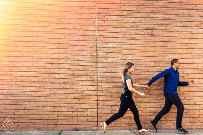 Vicosa Brazil Couple running together during prewedding portrait shoot against a brick wall.