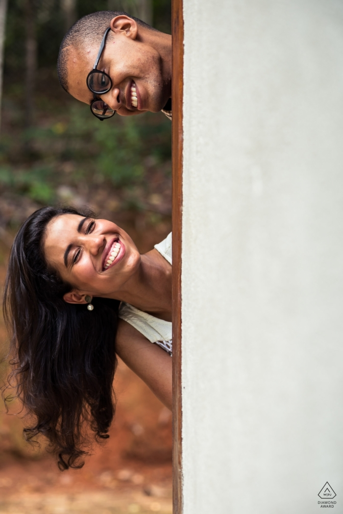 Vicosa Brazil Engagement Photographer: Couple with their faces coming out of the wall