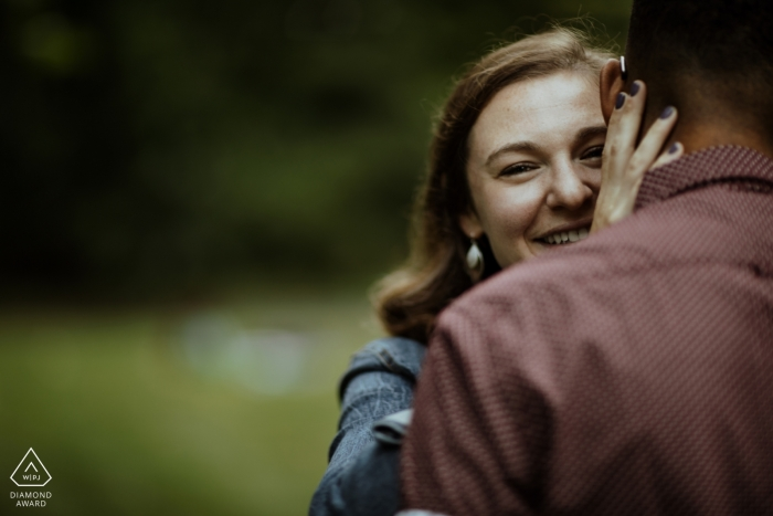 Boston, MA Engagement Shoot - She peeks over his shoulder during a hug at their Jamaica Pond session