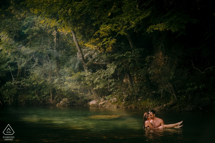 Tuscany, Val di Merse engagement portrait shoot with a ray of light through the trees