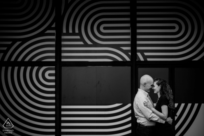 Crystal City, VA engagement photo session in black and white   A couple laughs together in front of a black and white striped window covering.
