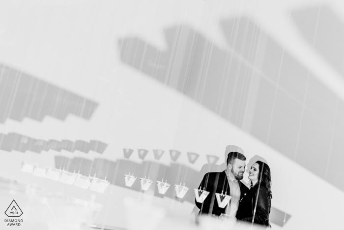 Una pareja se ríe juntos en una instalación de arte colgante prisim. Fotografía de compromiso en la National Gallery of Art East Wing