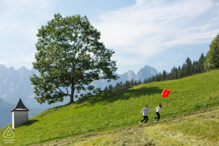 Gosau engagement session of a couple running through the Austrian mountains with red balloons
