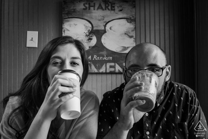 Helen, GA engagement portrait - Couple drinking coffee below Share sign.