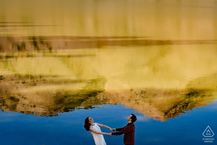 CARSON CITY ENGAGEMENTS - Portraits of Couple by the Water with Reflection of the Mountains.