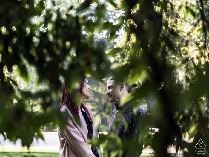 Milan, Italie photos de fiançailles prises à travers les arbres verts bas.