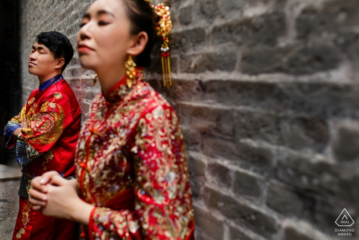 Ho Chi Minh City-Paarporträts im Trachtenkleid gegen eine Backsteinmauer.