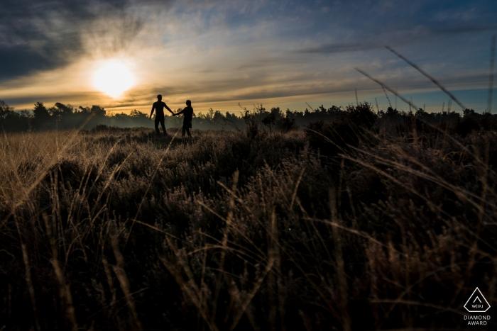 Rucphense Heide, Rucphen Pre Portraits de mariage - Un couple marchant dans la lande, à la lumière du matin, avec de jolies couleurs.